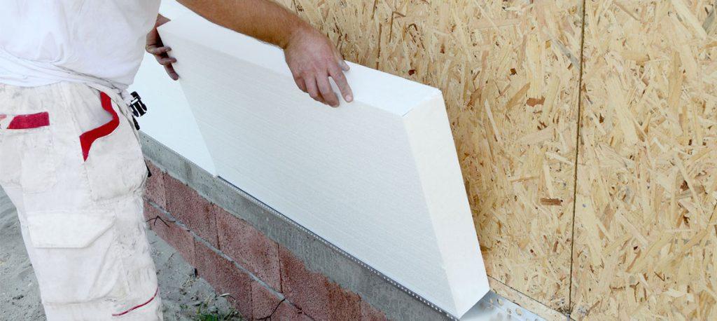 Maler bringt Styropor Dämmung an einer Fassade an
